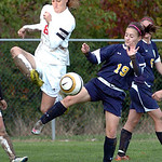 Elyria's #8 Ashley Curtis tries to clear the ball from North Ridgeville's #19 Lauren Ginley.
