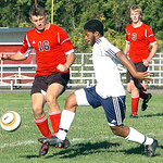 Oberlin's #5 Dorian Boye-Doe tries to work the ball past Firelands' #16 Daniel Klesta.