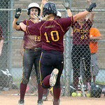 Avon Lake's #18 Morgan Turner congratulates Avon Lake's #10 Paige Collins as she leaps onto home plate to score.