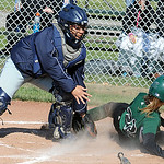 Elyria Catholic's Emily Hastings is safe at the plate before Lorain's Haley McCall can tag her. STEVE MANHEIM/CHRONICLE