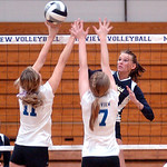 North Ridgeville's #13 Maddie Schauer spikes the ball past Midview's #11 Cassie Haight and #7 Meghan Higley.