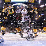 Boston Bruins defenseman Dennis Seidenberg (44), of Germany, and center Patrice Bergeron (37) check Chicago Blackhawks left wing Brandon Saad, center, in front of the goal during the second  …
