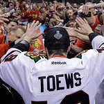 Fans give high-fives to Chicago Blackhawks center Jonathan Toews after the Blackhawks beat the Boston Bruins 3-2 in Game 6 of the NHL hockey Stanley Cup Finals Monday, June 24, 2013, in Bost …