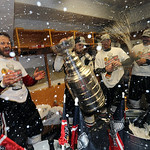Chicago Blackhawks center Michal Handzus, left, of Slovakia, celebrates with the Stanley Cup and teammates in the locker room after his team beat the Boston Bruins 3-2 in Game 6 of the Stanl …