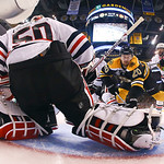Chicago Blackhawks defenseman Johnny Oduya, right, of Sweden, knocks Boston Bruins left wing Daniel Paille (20) into the crease in front of Blackhawks goalie Corey Crawford (50) during the f …