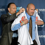 Cleveland Indians executive vice president and general manager Mark Shapiro, left, helps manager Manny Acta put his jersey on at a news conference Monday, Oct. 26, 2009, in Cleveland. Acta, …