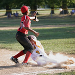 The Cuyahoga Falls player reaches in safe before the ball reaches third basemen Devonte Bowens of Elyria West. photo by Ray Riedel.