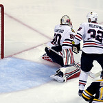 The puck from Boston Bruins' Daniel Paille, not seen, soars into the net past Chicago Blackhawks goalie Corey Crawford (50) and defenseman Michal Rozsival (32), of the Czech Republic, during …