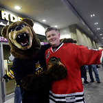 Boston Bruins fan Matt Kona, left, of Boston, wearing a bear costume poses with Chicago Blackhawks fan T.J. Budka, right, of Ayer, Mass., outside TD Garden in Boston before Game 3 of the NHL …