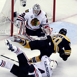 Chicago Blackhawks defenseman Niklas Hjalmarsson (4), of Sweden, takes down Boston Bruins left wing Daniel Paille (20) in front of Blackhawks goalie Corey Crawford (50) during the second per …