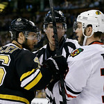 An official moves to separate Boston Bruins center David Krejci (46), of the Czech Republic,  and Chicago Blackhawks center Jonathan Toews (19) during the first period in Game 3 of the NHL h …