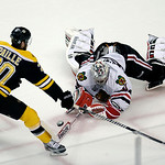 Chicago Blackhawks goalie Corey Crawford, right, knocks the puck away from Boston Bruins left wing Daniel Paille (20) during the first period in Game 3 of the NHL hockey Stanley Cup Finals i …