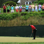 Tiger Woods attempts a putt on the 11th hole green as spectators watch from a property above during the final day of the U.S. Open Sunday, June 16, 2013 at the Merion Golf Club in Ardmore, P …