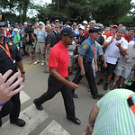 Tiger Woods is escorted through crowds of spectators as he makes his way to the 13th hole during the final day of the U.S. Open Sunday, June 16, 2013 at the Merion Golf Club in Ardmore, Pa.  …