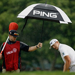 Hunter Mahan lines up a putt on the 13th hole as caddie John Wood holds an umbrella during the fourth round of the U.S. Open golf tournament at Merion Golf Club, Sunday, June 16, 2013, in Ar …