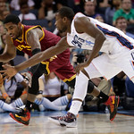 Cleveland Cavaliers' Kyrie Irving, left, and Charlotte Bobcats' Michael Kidd-Gilchrist, right, chase a loose ball during the second half of an NBA basketball game in Charlotte, N.C., Wednesd …