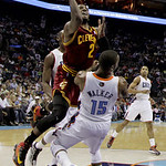 Cleveland Cavaliers' Kyrie Irving (2) drives into Charlotte Bobcats' Kemba Walker (15) during the first half of an NBA basketball game in Charlotte, N.C., Wednesday, April 17, 2013. Irving w …