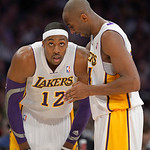 Los Angeles Lakers guard Kobe Bryant, right, chats with center Dwight Howard during the first half of their NBA basketball game against the Cleveland Cavaliers, Sunday, Jan. 13, 2013, in Los …