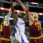 Los Angeles Clippers guard Chris Paul, center, drives between Cleveland Cavaliers forward Tyler Zeller, left, and center Anderson Varejao (17) in the first half of an NBA basketball game, Mo …