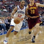 Philadelphia 76ers' Evan Turner (12) drives past Cleveland Cavaliers' Chris Quinn (20) during an NBA basketball game, Sunday, April 14, 2013, in Philadelphia. The 76ers won 91-77. (AP Photo/ …
