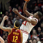 Chicago Bulls guard Jimmy Butler (21) shoots as Cleveland Cavaliers guard D.J. Kennedy (12) looks on during the first half of an NBA basketball game in Chicago, Thursday, April 26, 2012. (AP …