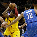 Cleveland Cavaliers' Kyrie Irving (2) tries to get past Orlando Magic's Nikola Vucevic (9), from Montenegro, and Orlando Magic's Tobias Harris (12) during the first quarter of an NBA basketb …