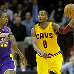 Cleveland Cavaliers' C.J. Miles (0) passes away from Los Angeles Lakers' Metta World Peace in an NBA basketball game Tuesday, Dec. 11, 2012, in Cleveland. (AP Photo/Mark Duncan)