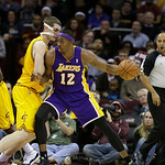 Los Angeles Lakers' Dwight Howard (12) drives on Cleveland Cavaliers' Tyler Zeller in an NBA basketball game Tuesday, Dec. 11, 2012, in Cleveland. (AP Photo/Mark Duncan)