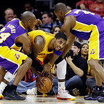 Los Angeles Lakers' Kobe Bryant, left, and Antawn Jamison, right, tries to wrestle the ball away from Cleveland Cavaliers' Kyrie Irving in the fourth quarter of an NBA basketball game, Tuesd …