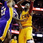 Cleveland Cavaliers' Kyrie Irving, right, shoots against Los Angeles Lakers' Jordan Hill (27) and Metta World Peace in the fourth quarter of an NBA basketball game, Tuesday, Dec. 11, 2012, i …