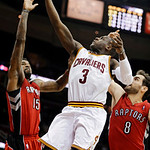 Cleveland Cavaliers' Dion Waiters (3) shoots between Toronto Raptors' Amir Johnson (15) and Jose Calderon (8), of Spain, in the fourth quarter of an NBA basketball game, Tuesday, Dec. 18, 20 …