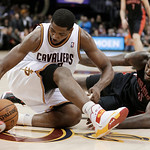 Cleveland Cavaliers' Tristan Thompson, left, and Toronto Raptors' Amir Johnson scramble for a loose ball during the fourth quarter of an NBA basketball game Wednesday, Feb. 27, 2013, in Clev …