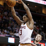 Cleveland Cavaliers' Tristan Thompson (13) dunks in front of Toronto Raptors' Jonas Valanciunas (17) during the second quarter of an NBA basketball game Wednesday, Feb. 27, 2013, in Clevelan …