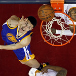 Golden State Warriors' Klay Thompson, left, flips in a shot against Cleveland Cavaliers' Kyrie Irving in the fourth quarter of an NBA basketball game Tuesday, Jan. 29, 2013, in Cleveland. Th …