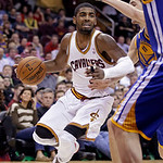 Cleveland Cavaliers' Kyrie Irving tries to drive past Golden State Warriors' Klay Thompson (11) and David Lee in the fourth quarter of an NBA basketball game Tuesday, Jan. 29, 2013, in Cleve …