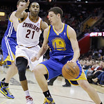 Golden State Warriors' Klay Thompson (11) drives on Cleveland Cavaliers' Wayne Ellington (21) in an NBA basketball game Tuesday, Jan. 29, 2013, in Cleveland. (AP Photo/Mark Duncan)