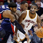 Atlanta Hawks' Josh Smith, left, fouls Cleveland Cavaliers' Kyrie Irving (2) as Hawks' Jeff Teague reaches in from behind in the third quarter of an NBA basketball game, Wednesday, Jan. 9, 2 …