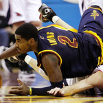 Cleveland Cavaliers' Kyrie Irving (2) flips over Atlanta Hawks' Kirk Hinrich, right, as they chase a loose ball in the second half of an NBA basketball game in Cleveland on Sunday, March 18, …