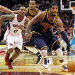 Cleveland Cavaliers' Kyrie Irving (2) drives into the lane past Atlanta Hawks' Jeff Teague (0) and Cavaliers' Samardo Samuels, rear, in the first quarter of an NBA basketball game in Clevela …