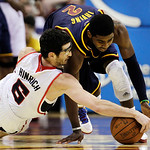 Atlanta Hawks' Kirk Hinrich (6) and Cleveland Cavaliers' Kyrie Irving (2) fight for a loose ball in the second quarter of an NBA basketball game in Cleveland on Sunday, March 18, 2012. (AP P …
