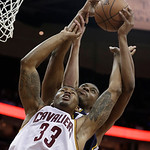 Cleveland Cavaliers' Alonzo Gee, front, and Utah Jazz's Derrick Favors go up for a rebound during the second quarter of an NBA basketball game Wednesday, March 6, 2013, in Cleveland. (AP Pho …