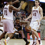 Utah Jazz's Mo Williams, center, trips as he tries to pass between  Cleveland Cavaliers' Tristan Thompson, left, and Tyler Zeller during the second quarter of an NBA basketball game Wednesda …