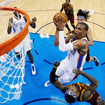Oklahoma City Thunder guard Russell Westbrook (0) shoots between Cleveland Cavaliers center Anderson Varejao, rear, and guard Daniel Gibson, bottom, in the first quarter of an NBA basketball …