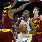 Golden State Warriors power forward Carl Landry, center, is defended by Cleveland Cavaliers small forward C.J. Miles (0) and power forward Jon Leuer (30) during the third quarter of an NBA b …