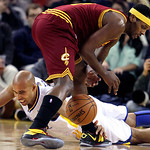 Golden State Warriors forward Richard Jefferson, bottom, reaches for the ball under Cleveland Cavaliers forward C.J. Miles during the first quarter of an NBA basketball game in Oakland, Cali …