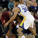 Cleveland Cavaliers point guard Kyrie Irving, left, tries to dribble as he is defended by Golden State Warriors shooting guard Stephen Curry (30) and power forward David Lee during the third …