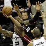 Miami Heat's Dwyane Wade shoots between San Antonio Spurs' Kawhi Leonard (2) and Tim Duncan (21) during the first half at Game 5 of the NBA Finals basketball series, Sunday, June 16, 2013, i …