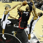 Miami Heat's Dwyane Wade (3) is defended by San Antonio Spurs' Tim Duncan (21) and Kawhi Leonard (2) during the first half at Game 5 of the NBA Finals basketball series, Sunday, June 16, 201 …