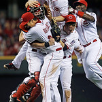 Cincinnati Reds starting pitcher Homer Bailey, front, is mobbed by catcher Ryan Hanigan, left, third baseman Todd Frazier, top, shortstop Zack Cozart,  and second baseman Brandon Phillips, r …