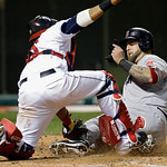 Boston Red Sox's Mike Napoli, right, beats the tag by Cleveland Indians catcher Carlos Santana to score from second on a single by Mike Carp in the seventh inning of a baseball game on Thurs …
